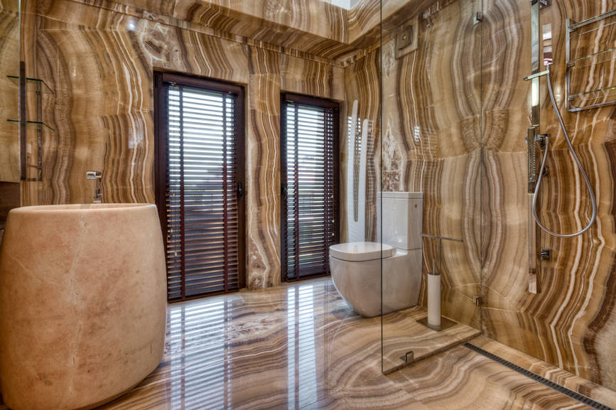 Contemporary primary bathroom with louvered windows and brown tiled flooring extending to the patterned walls for a cohesive look. It includes a large sink pedestal and a toilet next to the walk-in shower.