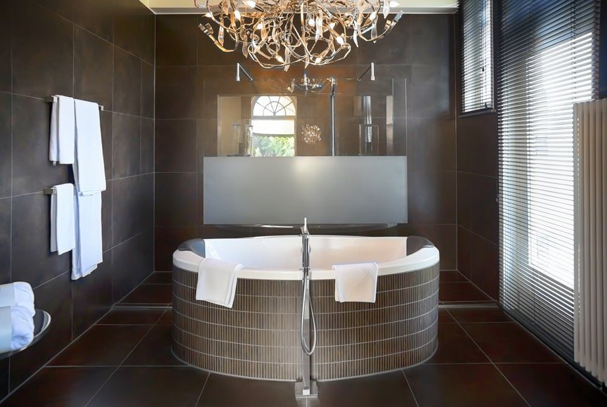 A stylish chandelier illuminates the deep soaking tub fixed in front of the walk-in shower that's enclosed in frameless glass panels. It is surrounded by brown tiled walls and glazed windows covered in white roller blinds.