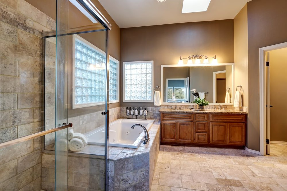 The brown primary bathroom features a wooden vanity and a deep soaking tub by the glass block windows. It is clad in stone brick tiles matching with the backsplash and limestone flooring.