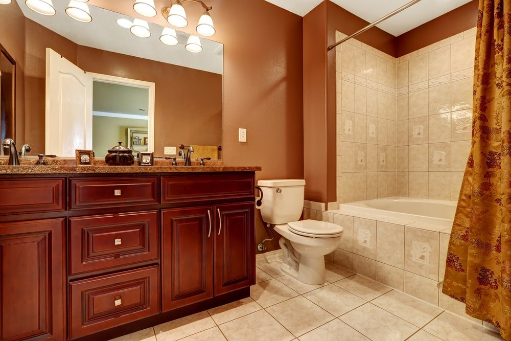 Warm master bathroom with a toilet and wooden vanity illuminated by warm sconces. There's a shower and tub combo on the side enclosed in a foliage print curtain.