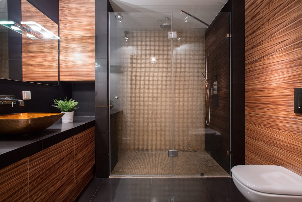 The sleek primary bathroom showcases a wall hung toilet and a vessel sink vanity that matches the brown walls. It includes a walk-in shower with mosaic tile backsplash extending to the flooring.