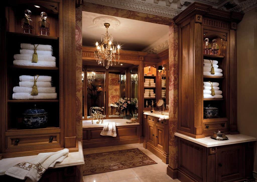 Wooden cabinets match the sink vanity and drop-in tub that's complemented by a classic rug. It is illuminated by a fancy crystal chandelier along with candle sconces mounted on the wall mirrors.
