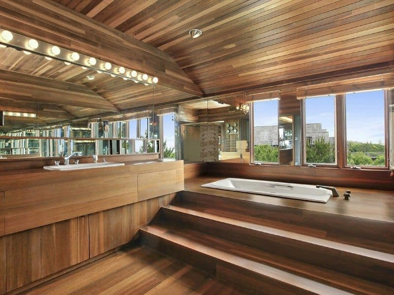 An all wood primary bathroom with a cohesive design featuring a sleek vanity under a frameless mirror along with a drop-in tub by the glass paneled windows overlooking the outdoor scenery.