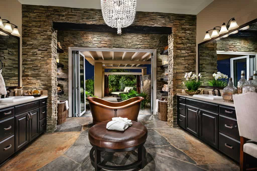 Brick accent walls add texture in this primary bathroom with facing sink vanities and a copper freestanding tub sitting across the round ottoman that's illuminated by a crystal chandelier.