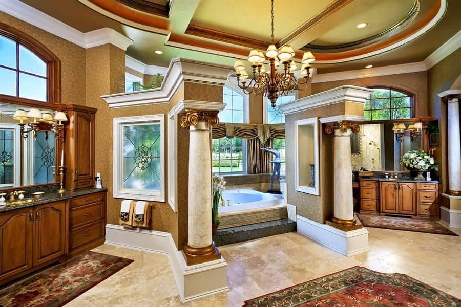 Luxury primary bathroom with marble columns and a fabulous chandelier that hung from the oval tray ceiling. It includes a drop-in tub, wooden vanities and classy rugs that lay on the beige tiled flooring.