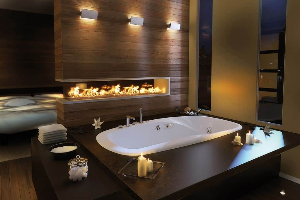 Ambient light from the glass sconces and modern fireplace creates a warm and cozy feel in this open bathroom situated in front of the comfy bed. It showcases a deep soaking tub with a dark wood bench on the side.