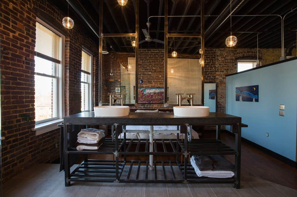 Industrial primary bathroom with red brick walls and a beamed ceiling mounted with glass pendant lights. It includes a dual vessel sink vanity over wide plank flooring.