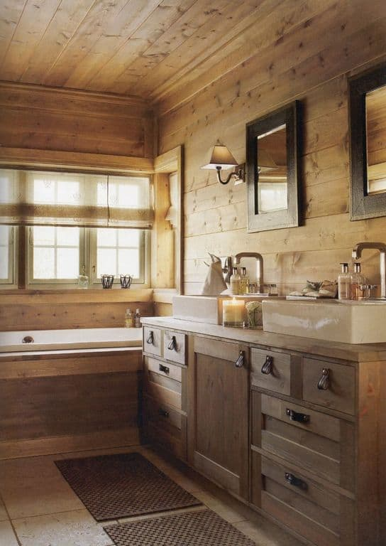 Clad in light wood planks, this primary bathroom offers a deep soaking tub and a dual vessel sink vanity that blends in with the walls. It has brown rugs and glazed windows covered in translucent roman shade.