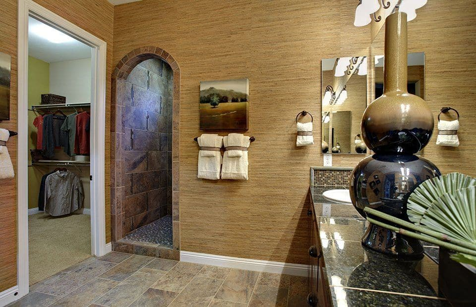 Small artworks add a nice accent to the brown walls that are mounted with frameless mirrors and wrought iron sconces. There's an open archway next to the walk-in closet leading to the shower area with brick backsplash.