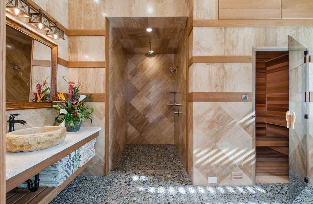 A wooden framed mirror hangs above the floating vanity that's topped with a vessel sink and a lovely flower vase. It is accompanied by a sauna room and a walk-in shower with pebble flooring.