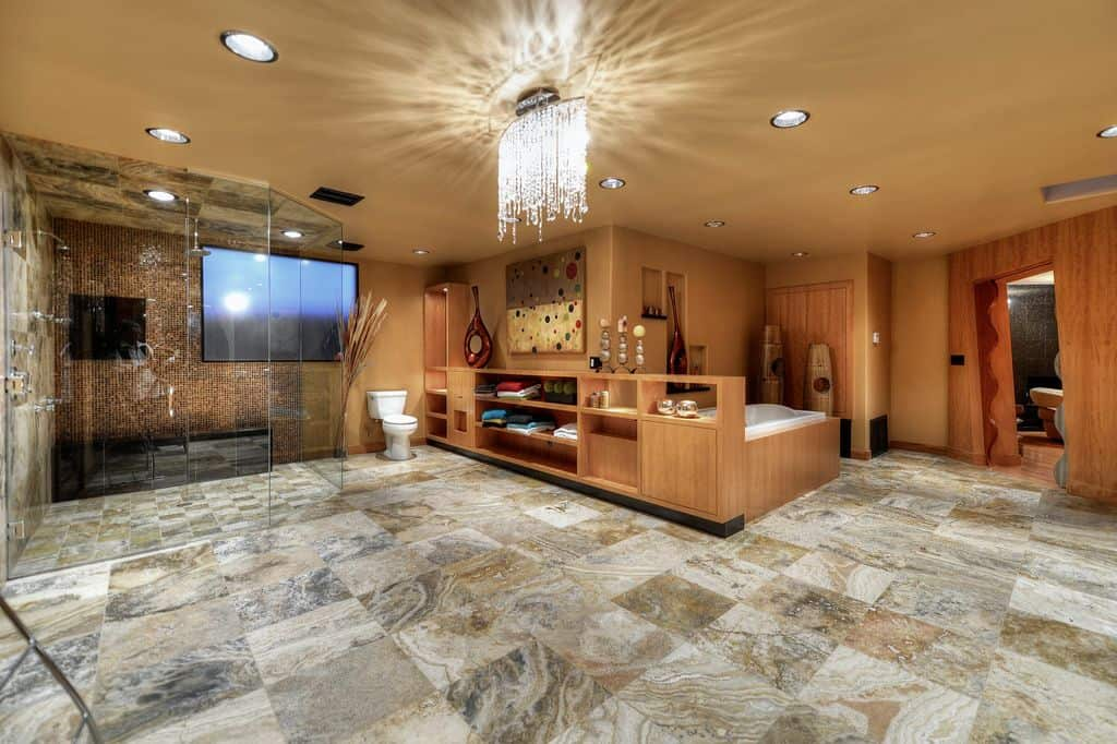 Spacious primary bathroom offers a walk-in shower and a toilet along with a deep soaking tub attached to the built-in cabinet. It is illuminated by recessed ceiling lights and a fancy crystal chandelier.
