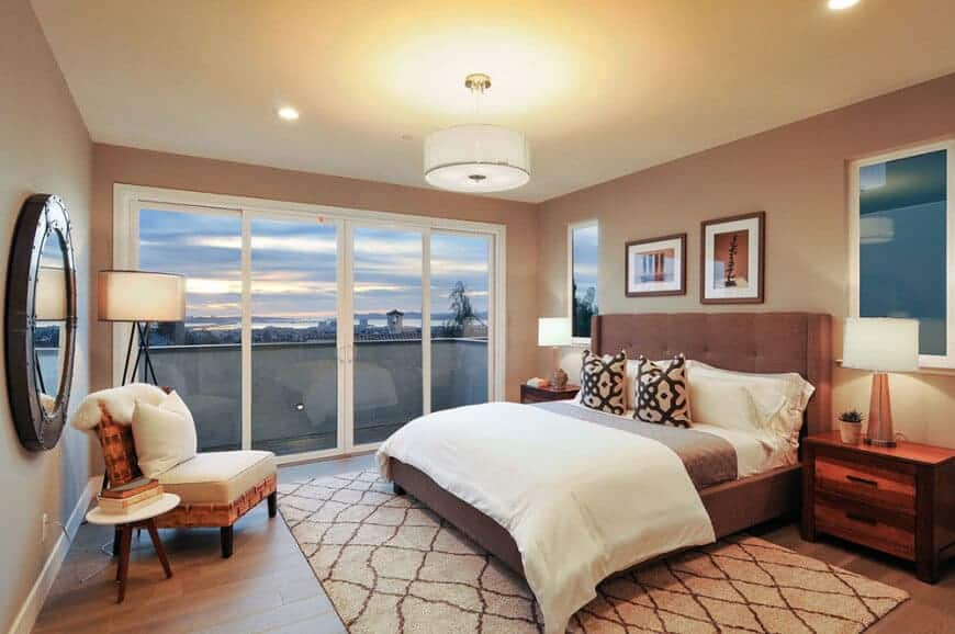 Primary bedroom featuring light brown walls and hardwood floors. The room has a modish bed setup lighted by table lamps on two bedside tables. The room also has a doorway leading to a private balcony.