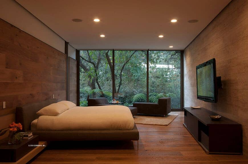 A spacious modern primary bedroom featuring hardwood floors and wooden walls. The room has glass windows overlooking the gorgeous surroundings. The room offers a cozy bed with a large widescreen TV set in front.