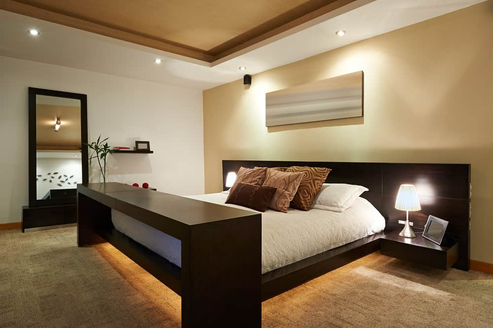 Primary bedroom boasting a modern bed setup with built-in bedside tables topped by table lamps. The room has a tray ceiling and carpeted flooring.