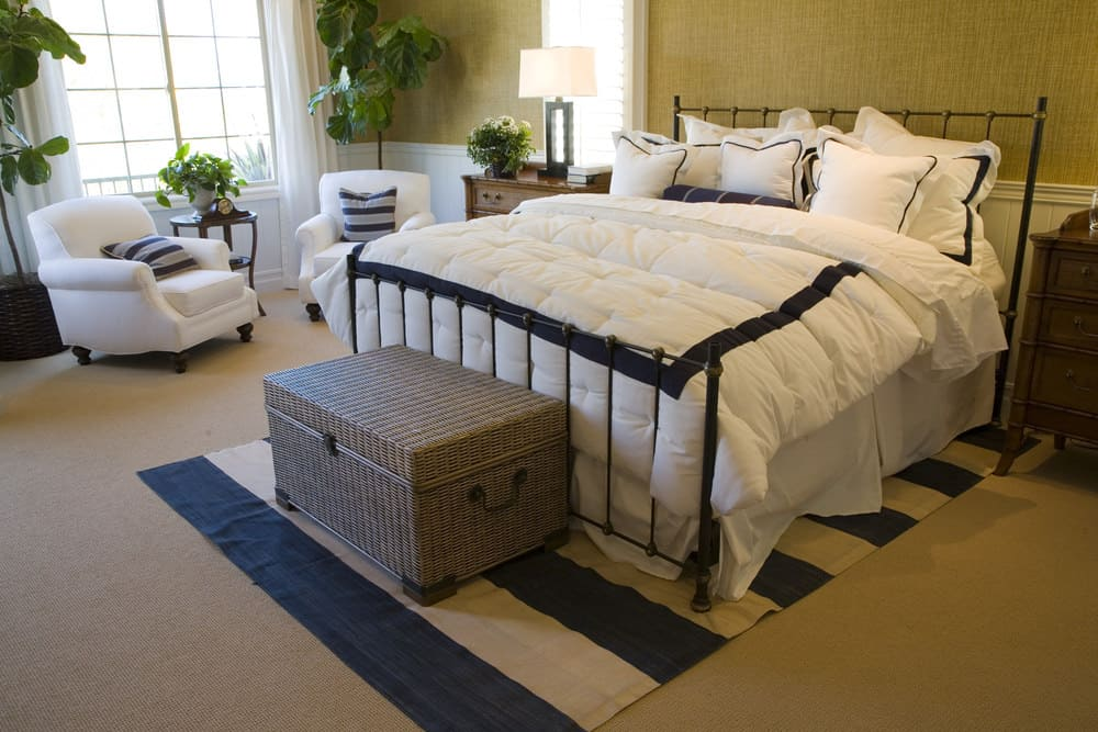 A close up look at this primary bedroom's large bed set with two chairs on the side. The room features brown walls and carpet flooring.