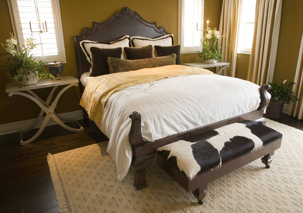 A focused shot at this primary bedroom's classy bed with stylish bedside tables topped by small indoor potted plants, surrounded by brown walls.