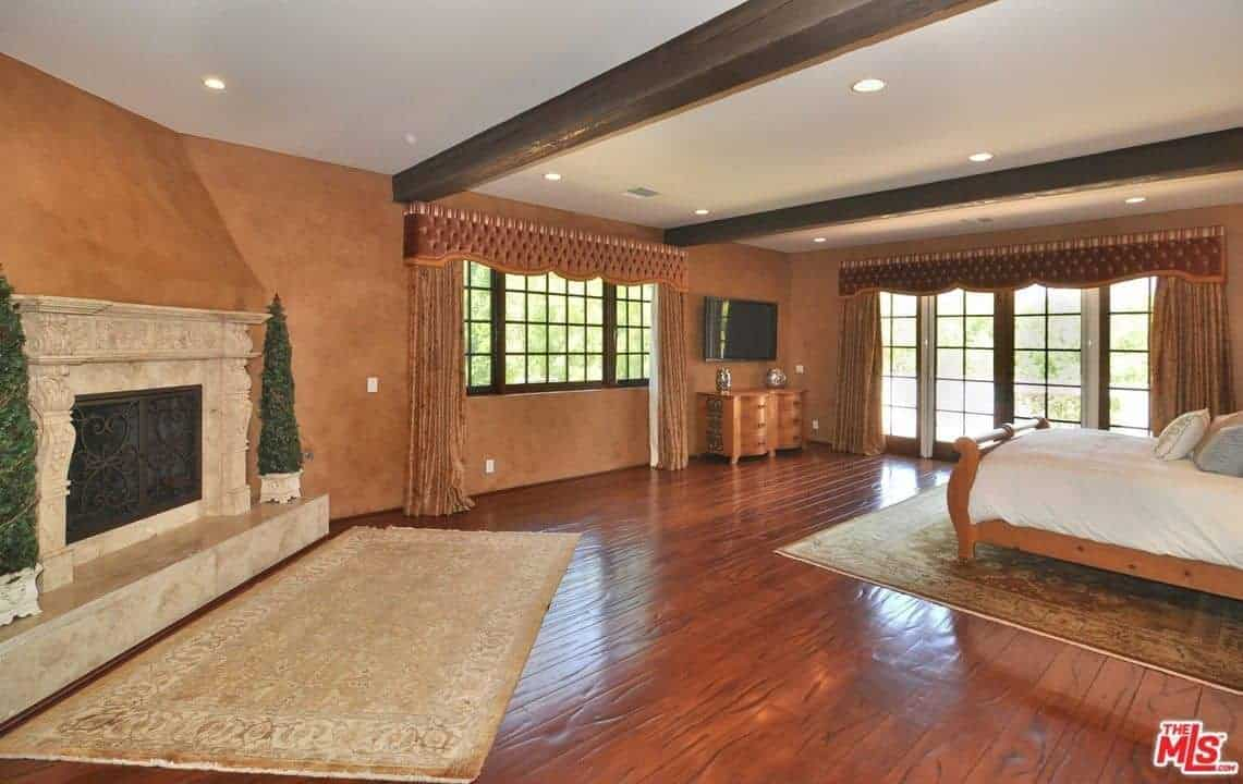 A spacious primary bedroom with hardwood flooring and a ceiling with beams. The room offers a nice bed and a fireplace surrounded by brown walls.