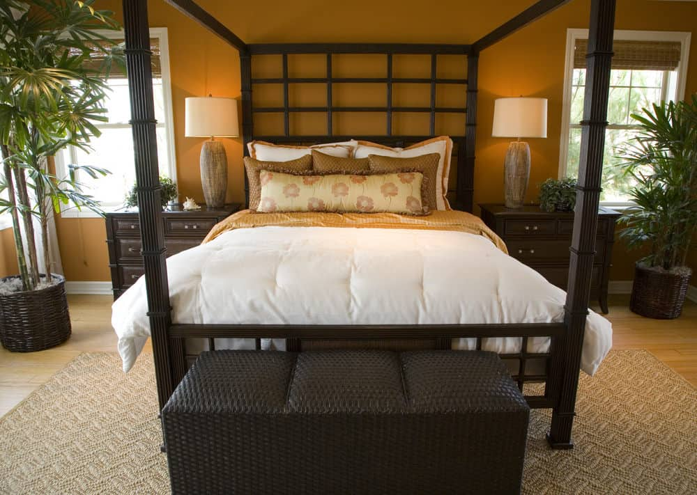 A close up look at this primary bedroom's gorgeous bed set lighted by cute table lamps on both sides and is surrounded by brown walls.