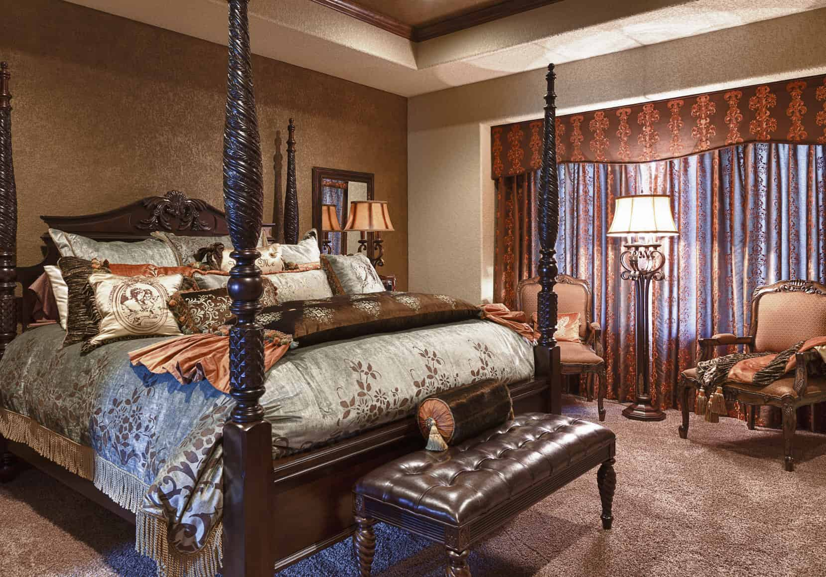 This primary bedroom features a gorgeous tray ceiling and brown walls, along with thick carpet flooring. The room has a classy bed with a sitting area on the side, lighted by a floor lamp.