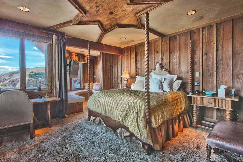 Primary bedroom with a stunning rustic design ceiling and wooden walls. The room also has thick carpet flooring. It offers a large bed, a study desk by the window and a living space in the corner.