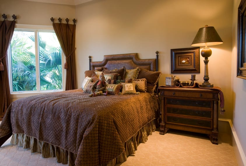 This primary bedroom boasts a cozy brown bed setup lighted by a brown table lamp on top of a classy bedside table. The room's glass windows feature brown window curtains as well.