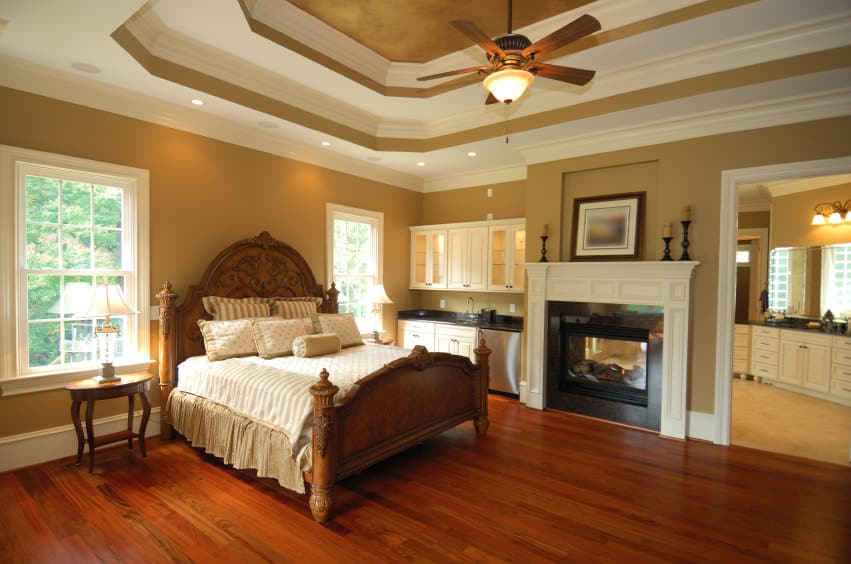 Primary bedroom featuring a stunning white and brown tray ceiling, along with brown walls and hardwood floors. The room offers a nice bed set and a fireplace on the side. There's a sink with cabinetry on the side. The room also has its own bathroom area.