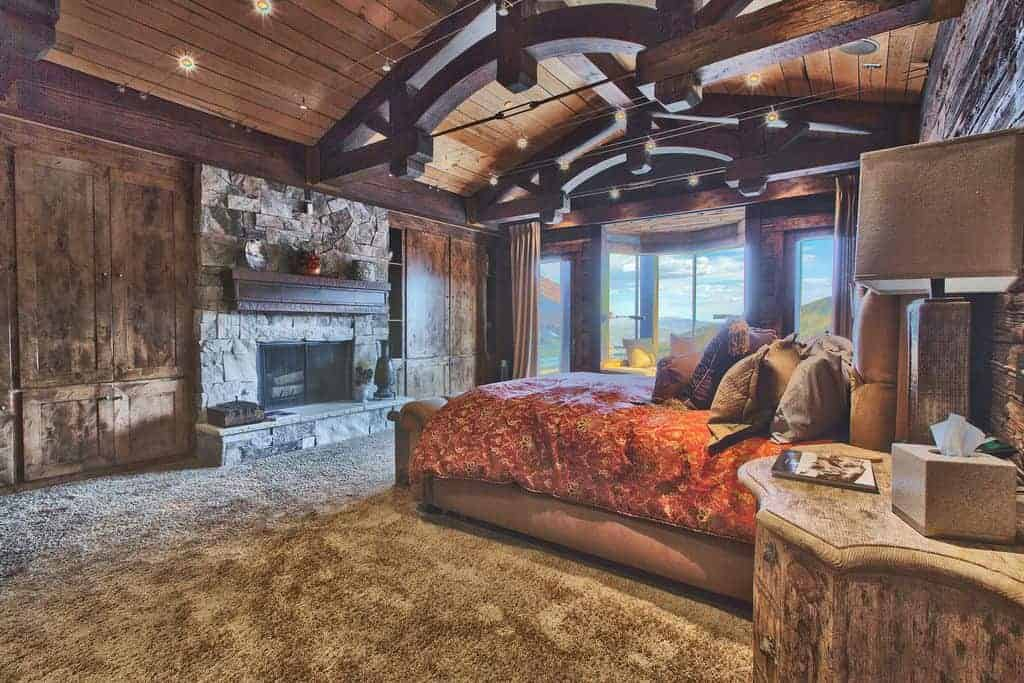 A spacious primary bedroom with a stylish wooden ceiling with large exposed beams. The room offers a gorgeous bed setup and a large stone fireplace set in front.