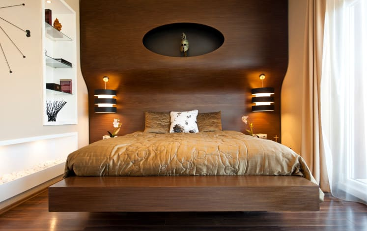 A focused shot at this primary bedroom's modern bed set with stylish wall lights. There are built-in shelves on the white wall beside the bed set.
