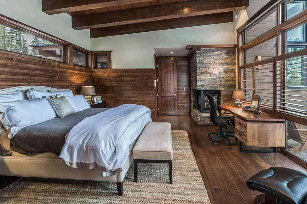 Rustic primary bedroom featuring hardwood flooring and a wooden ceiling with large beams. The room offers a massive comfy bed along with a stylish wooden office table by the windows with a stone fireplace in the corner.