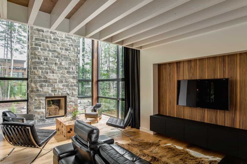 This is the entertainment area beside the living room area that has a high ceiling and a stone fireplace flanked with glass walls. These bring in natural lights that illuminate the white ceiling that has exposed wooden beams to contrast the black leather couch and the black entertainment system.