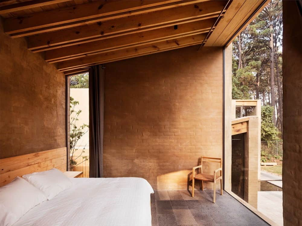 This is a simple and cozy bedroom with a wooden platform bed that has white sheets and pillows illuminated by the natural lights coming in from the large glass wall across from it. This is connected to the wooden shed ceiling with exposed beams complemented by the earthy brown brick walls.
