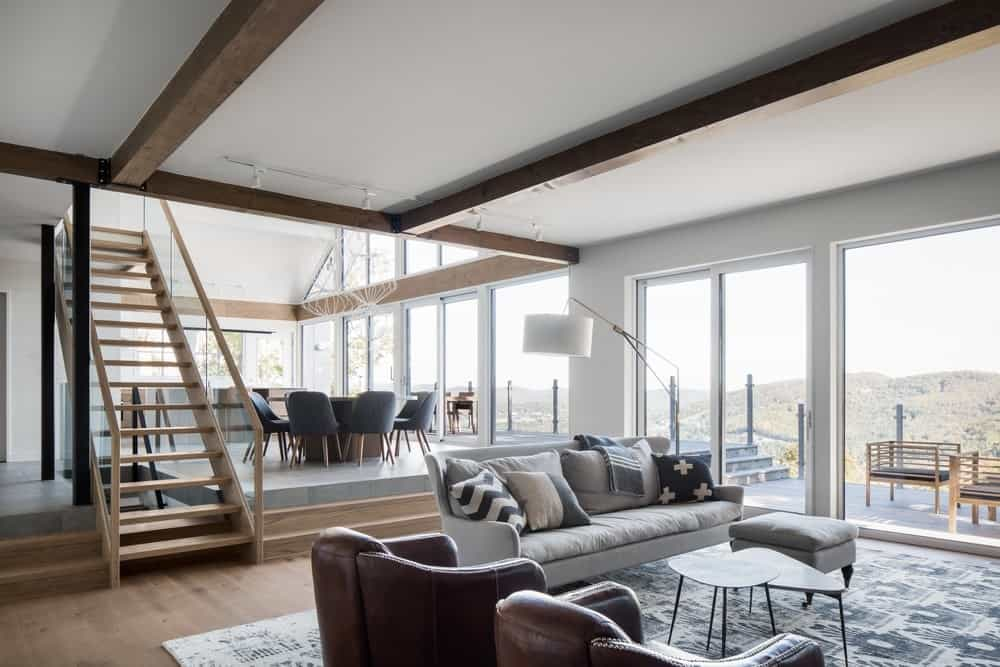 The brightness of this open-style great room is due to the glass walls that bring in an abundance of natural lights. This brightens the gray sofa and the pair of dark brown leather armchairs beside it. These chairs match with the dark wooden exposed beams of the white ceiling.