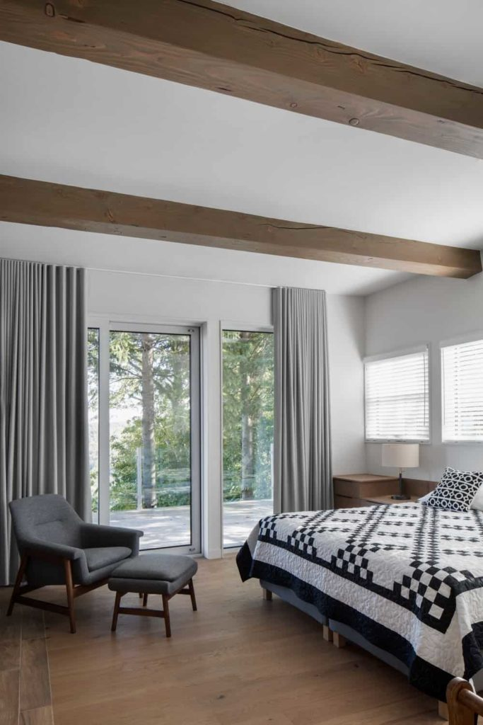 This primary bedroom has dark hardwood flooring that blends well with the exposed wooden beams of the ceiling. This stands out against the whiteness of the ceiling and walls that are further illuminated by the windows that contrasts the dark gray elements.