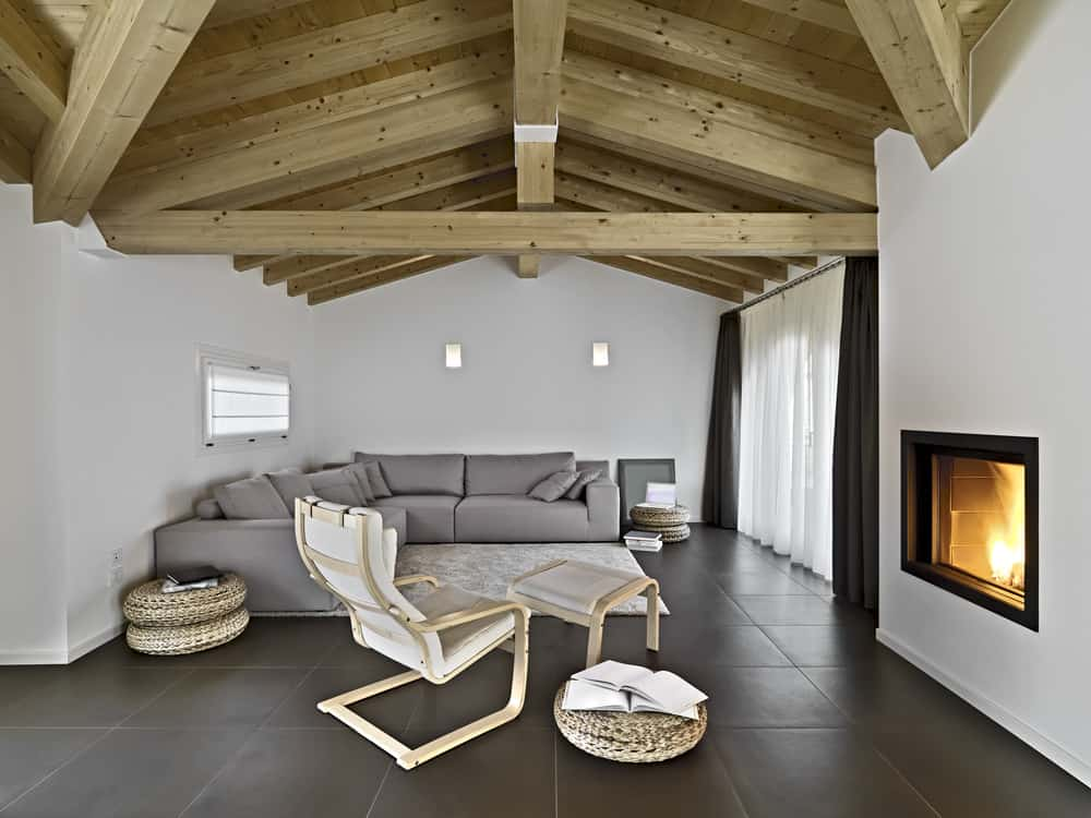 This is a charming living room with a wooden cathedral ceiling dominated by the large exposed wooden beams. This wooden ceiling works well with the fireplace in providing a cozy and comfortable environment for those enjoying the large L-shaped sectional gray sofa.