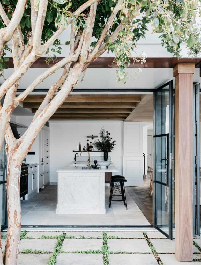 This is the view of a beautiful kitchen from outside the open glass doors. You can see here that the bright white hue that dominates the floor, walls and cabinetry are balanced by the wooden ceiling that has exposed wooden beams matching the column outside.