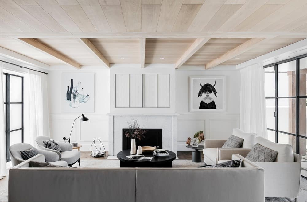 The glass windows on both sides of this living room give its white walls a natural brightness as well as its light gray sofa set. This is complemented by the charming wooden ceiling with exposed wooden beams that are only above the area of the living room.