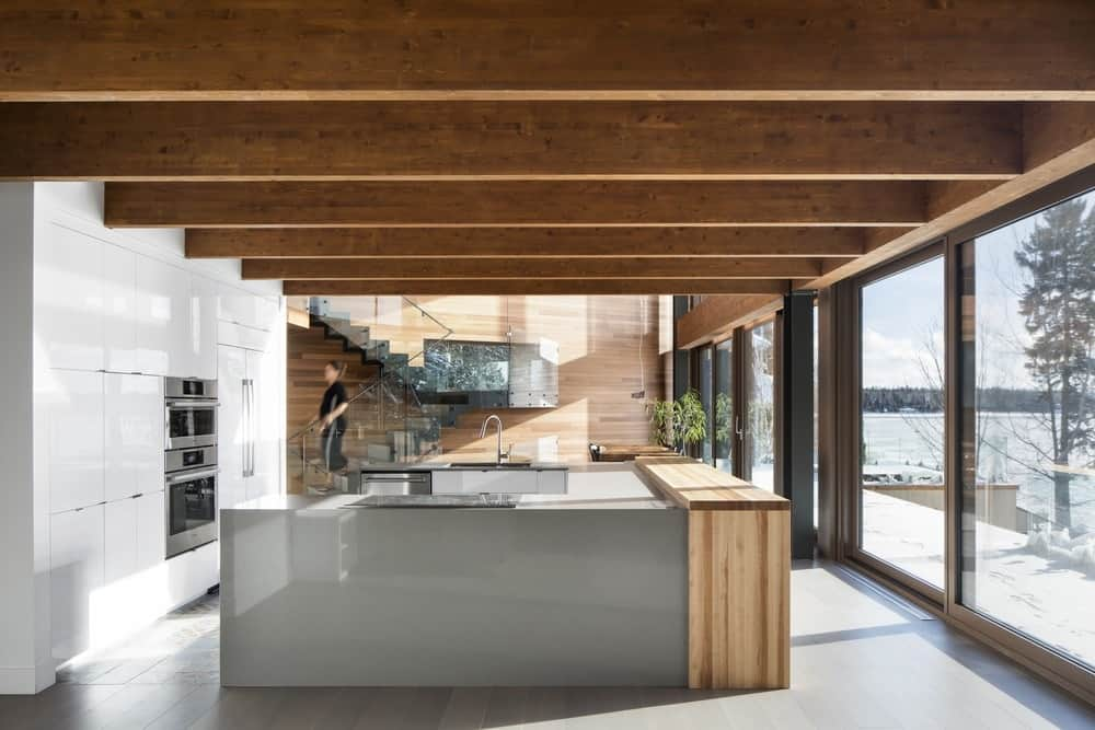 This is a modern kitchen with sleek and smooth white surfaces on its cabinets and a large U-shaped kitchen island in the middle. These are augmented by the large glass sliding doors on the side and the wide wooden ceiling that has exposed wooden beams.