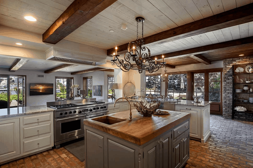 The earthy tone of the brick flooring is a nice complement to the classic tone of the gray wooden kitchen island and the off-white wooden L-shaped kitchen peninsula. This is mirrored by the wooden shiplap ceiling that is adorned with exposed wooden beams and a wrought iron chandelier.
