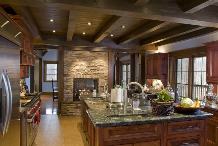 This is a charming kitchen that has a large column of stone that houses the fireplace next to the large kitchen island that has wooden cabinets and drawers matching the other cabinetry of the kitchen that is complemented by the dark wooden exposed beams of the ceiling.