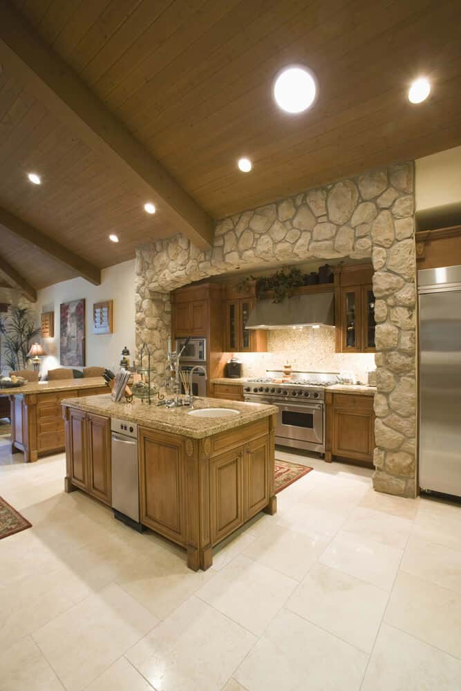 The wooden cathedral ceiling is dotted with several recessed lights of different sizes. This makes the thick wooden beams stand out as it is complemented by the textured stone arch of the cooking area with cabinetry matching the tone of the ceiling.