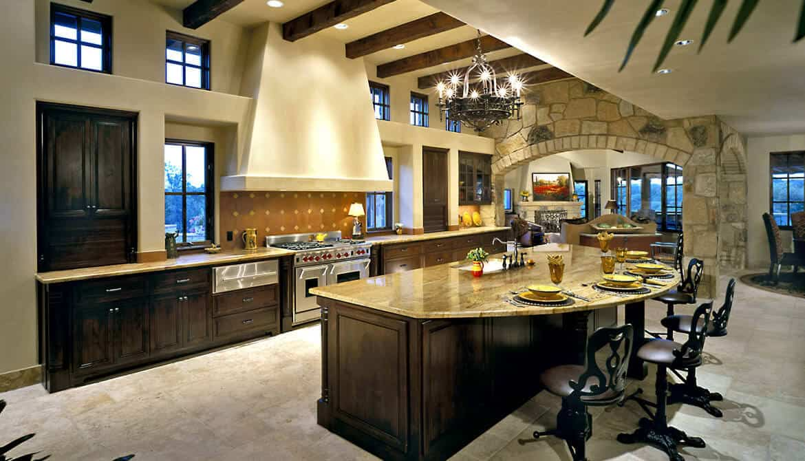 The high ceiling of this elegant kitchen is dominated by the dark contrast of the exposed wooden beams against the beige tone of the ceiling extending to the walls and the vent hood over the stainless steel stove top oven. This is across from the large half-circle kitchen island.