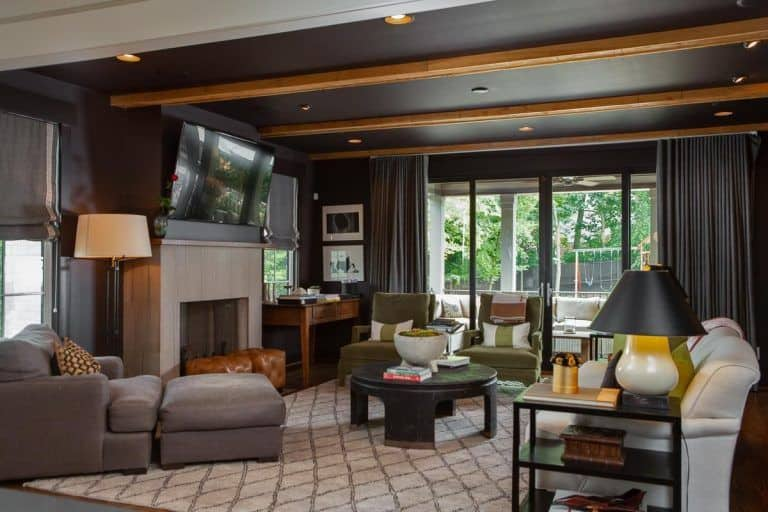The highlight of this charming living room is the beautiful pitch black ceiling that is adorned with bright wooden beams along with several recessed lights. This serves as a nice background for the living room that has a large fireplace and various cushioned sitting areas around a black coffee table.