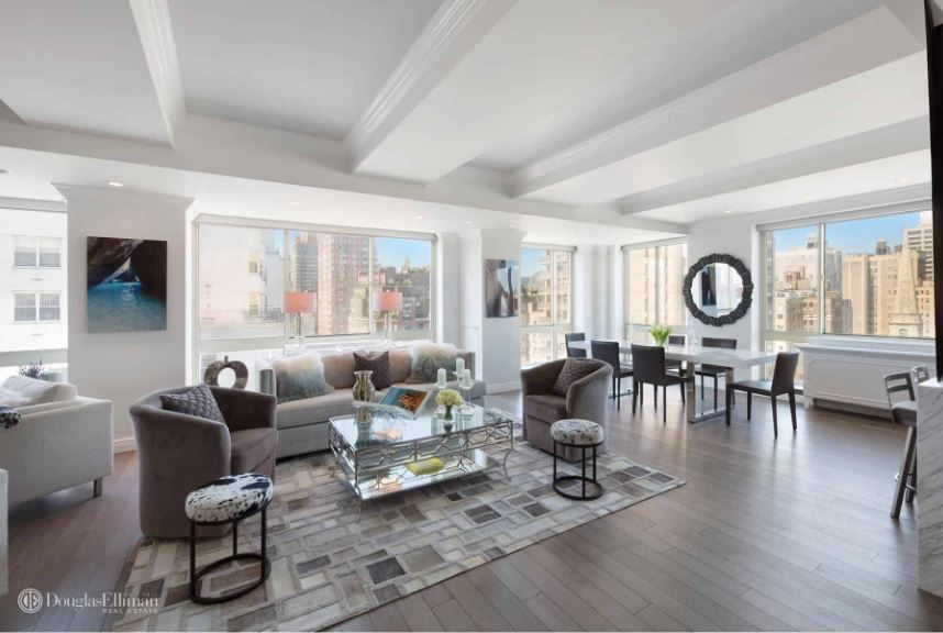 The gray patterned area rug that marks the area of the living room on the hardwood flooring is a good match for the cushioned sofa set brightened by the tall glass walls. These also illuminate the white ceiling and its thick exposed beams.
