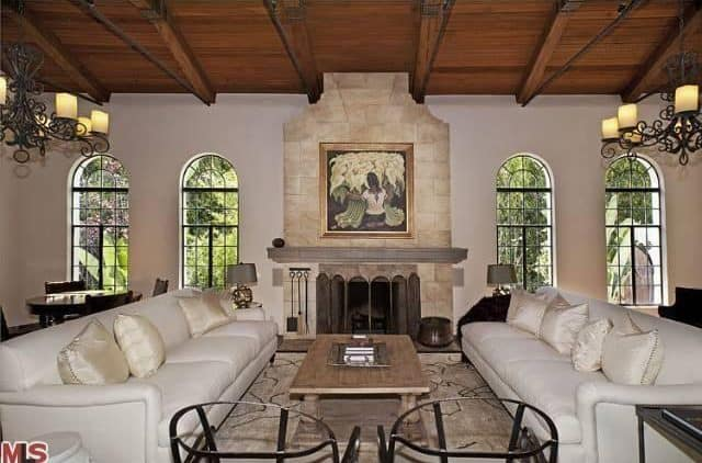 The two white leather sofas are flanking a small wooden coffee table across from the fireplace that is inlaid within a tall beige marble panel that reaches to the wooden ceiling. This supports the two wrought iron chandeliers through its exposed wooden beams.