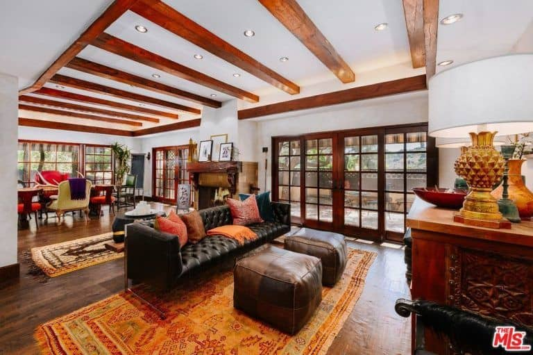 This is a luxurious living room area that is merely a part of the large room that also houses the dining area on the far side. These are both underneath the bright white ceiling with exposed wooden beams that match with the frames of the glass doors and the hardwood flooring topped with a an orange patterned area rug by the black leather couch.