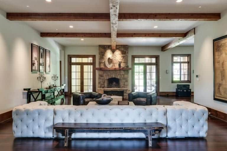 The dark hardwood flooring of this living room is contrasted by the brilliant tufted U-shaped sectional sofa. This is paired with a couple of black leather cushioned armchairs by the fireplace that is inlaid with stone complemented by the rustic wooden beams of the white ceiling.
