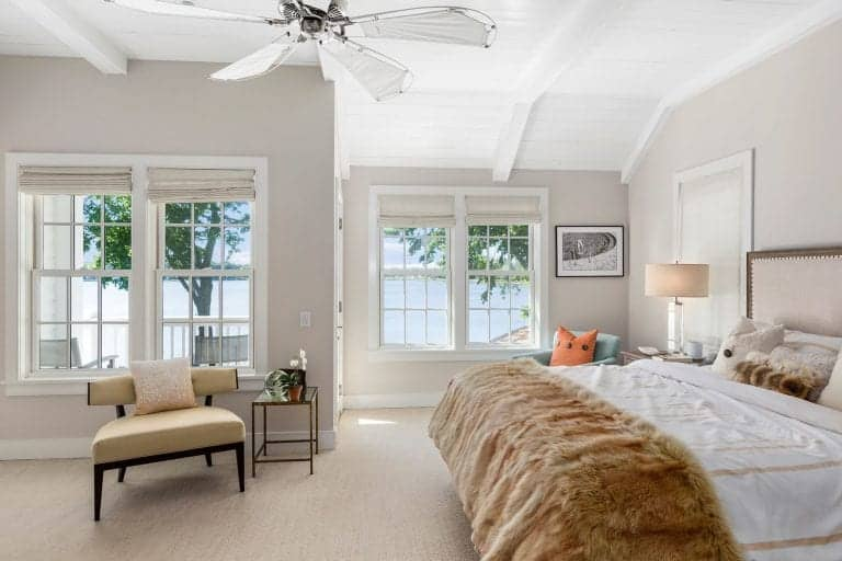 The highlight of this bright bedroom is the beautiful paradise showcased by the tall glass windows. This is a nice background for the light gray walls, beige carpeted flooring and the brilliant white shiplap ceiling with white exposed beams.