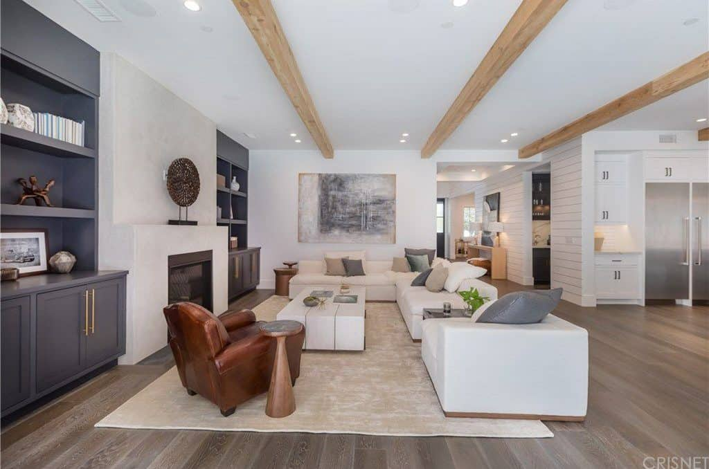 The off-white L-shaped sectional sofa matches with the wooden coffee table of the same tone. These are facing a fireplace that is embedded into the white wall that blends with the white ceiling that is adorned with large exposed wooden beams.