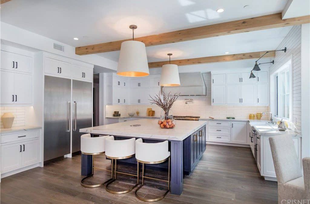 This is a bright and white kitchen with enough space for a large blue wooden kitchen island in the middle of the hardwood flooring. This matches well with the wooden exposed beams that contrast the ceiling and the white cabinetry.
