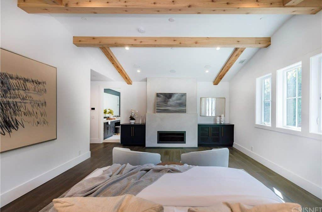 This is the view from the bed of this bright and airy primary bedroom. There is a couple of cushioned armchairs at the foot of the bed that stands out against the dark hardwood flooring. This flooring matches with the exposed wooden beams of the ceiling and contrasts the white walls adorned with a large abstract art on the side of the bed.